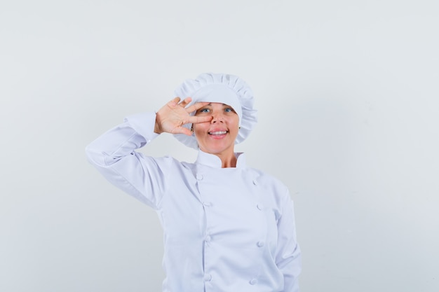 Woman chef in white uniform showing v-sign on eye and looking confident