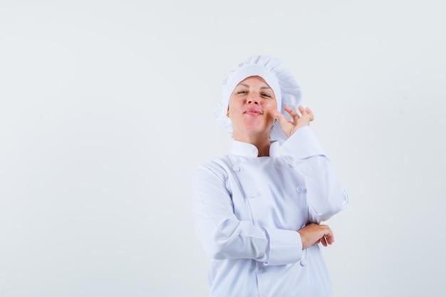 Chef donna in uniforme bianca che mostra il gesto della chiusura lampo e cerca di spazio per il testo