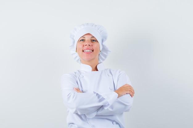 Chef donna in uniforme bianca in piedi con le braccia incrociate e guardando fiducioso