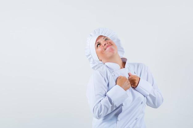 Chef donna che desidera qualcosa con le mani sul petto in uniforme bianca e sembra speranzoso