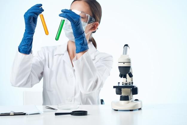 여자 화학자는 실험실 연구 현미경을 분석합니다