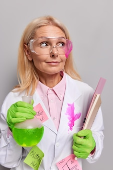 Woman chemist conducts scientific experiment holds flask with green liquid and notepad wears transparent glasses and white coat analyzed substance poses indoor