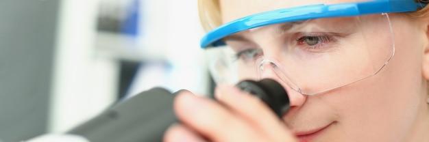 Женщина-химик в защитных очках, глядя через микроскоп