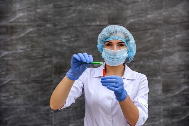 Женщина-химик переливает вещество из одной пробирки в другую, проводя эксперимент