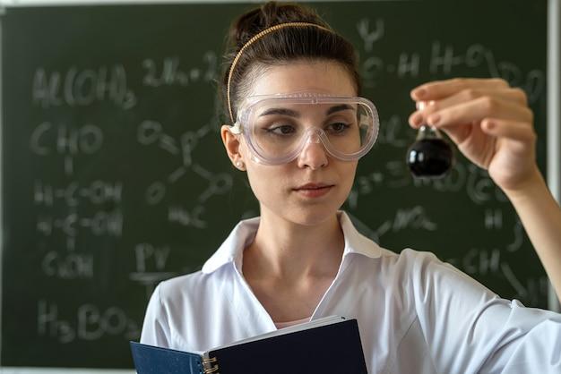 女性化学の先生は、化学式で黒板に対してガラスフラスコ内の液体を混合します