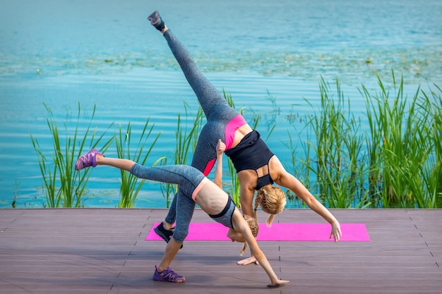 Woman and child doing handstand exercise on the grass near the lake. yoga nature concept