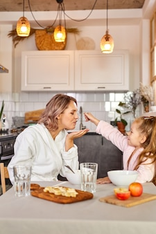 Woman and child girl have breakfast in the kitchen at home, beautiful family sit together having meak, enjoying morning together, have fun, smile