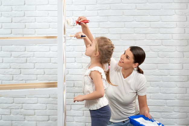 Woman and child refreshing wooden shelves with white paint