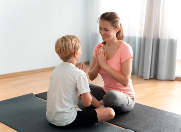 Donna e bambino sul tappetino da yoga inquadratura completa