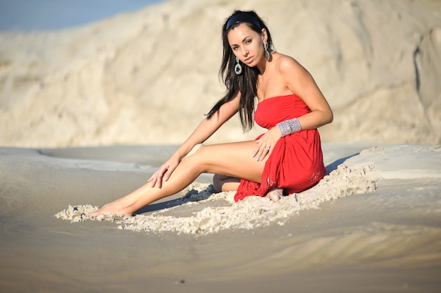 Woman chilling on the sand in red dress