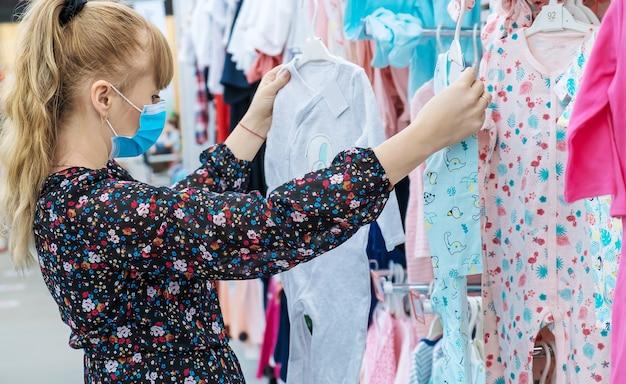 Женщина выбирает детскую одежду в магазине. выборочный фокус. магазин.