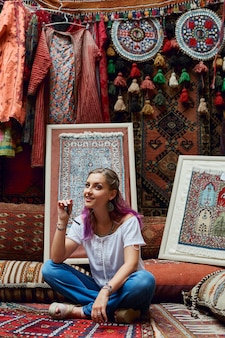 Женщина выбирает ковер на рынке