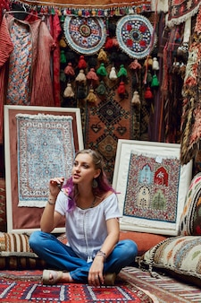 Woman chooses carpet at the market.
