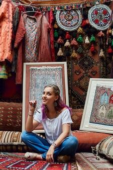 Woman chooses carpet at the market.