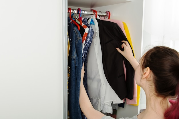 Woman chooses clothes in closet