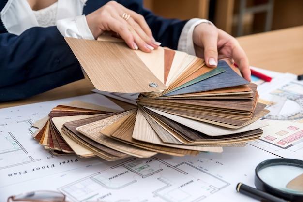 女性は現代の家のためにデザイナーの木の材料を選びます