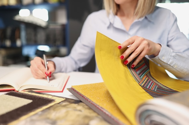 Woman chooses fabric with pattern for upholstery in interior of store fabric catalog concept