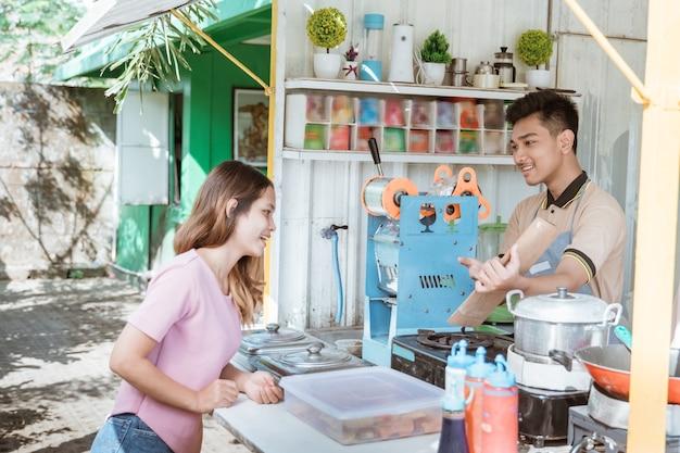 Женщина выбирает еду из меню, которое приносит продавец