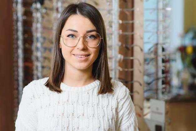 Женщина выбирает очки в магазине. брюнетка в белом свитере покупает очки.
