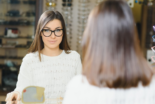 Woman chooses glasses in the store.
