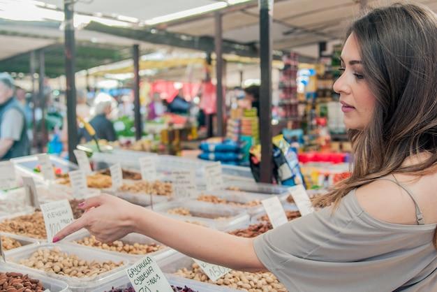 여자는 시장 견과류와 말린 과일을 선택합니다. 유기농 견과류를 선택하는 젊은 여자를 웃 고. 식료품가 게에서 무게로 다양 한 견과류를 구입하는 여자