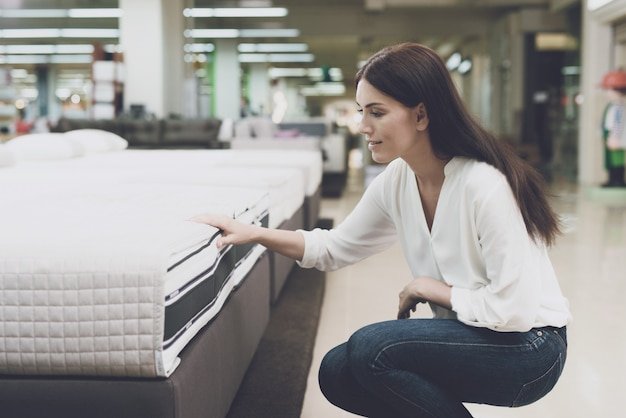 A woman chooses a mattress in a store.