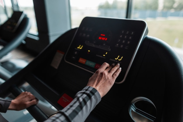 Woman chooses a mode on a treadmill before jogging in a gym, close up