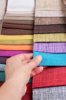 女性はテーブルのクローズアップで色の生地のサンプルを選択します