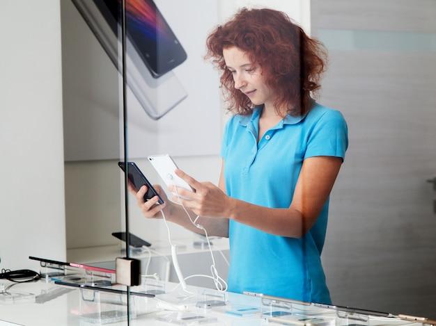 여자는 가게에서 스마트 폰을 선택