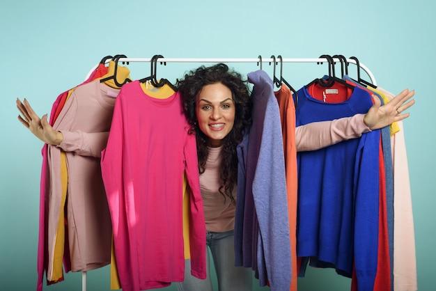 女性は店で買う服を選びます。ショッピングと買い物中毒の概念。