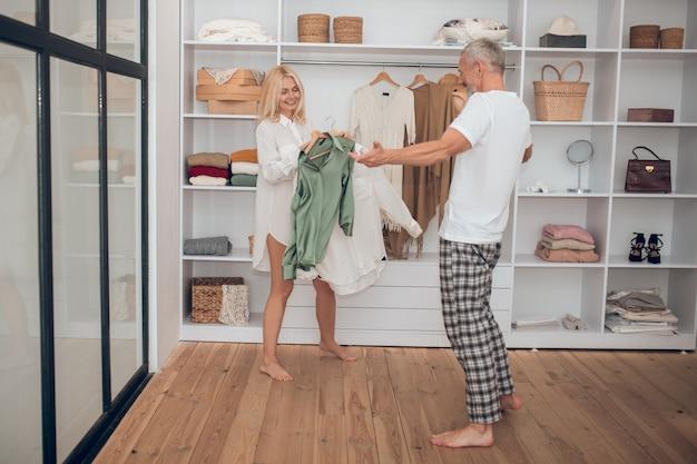 Женщина выбирает платье в гардеробе и показывает мужу