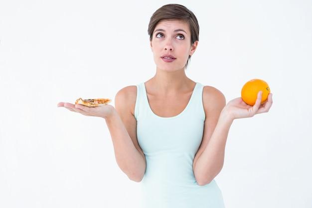 ピザとオレンジの間で選ぶ女性