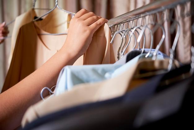 Женщина выбирает блузку в магазине