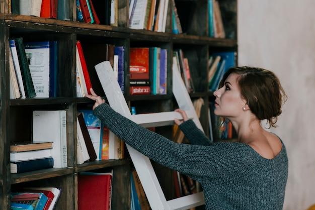 女性は棚から本を選ぶ
