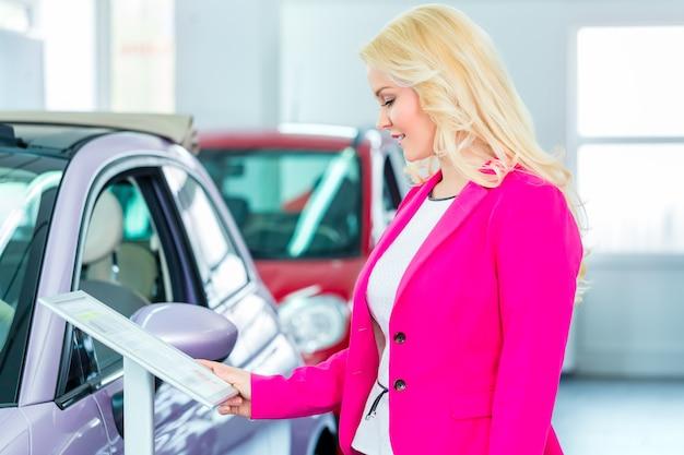 Woman choosing car for buying in dealership