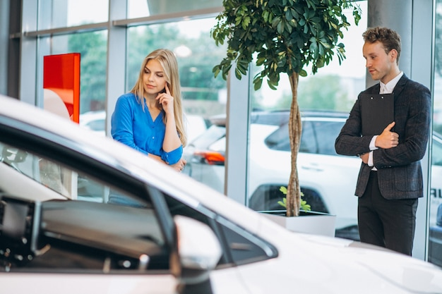 Woman choosing a car in a car showroom