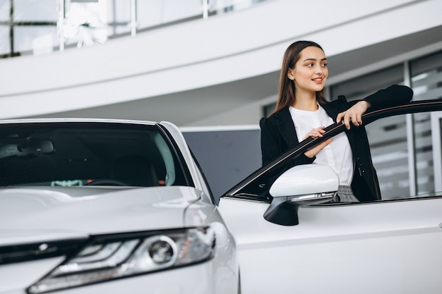 Woman choosing a car in a car showroom