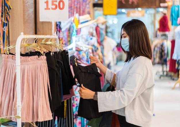 Женщина, выбирая одежду в торговом центре и носить медицинскую маску для профилактики от коронавируса