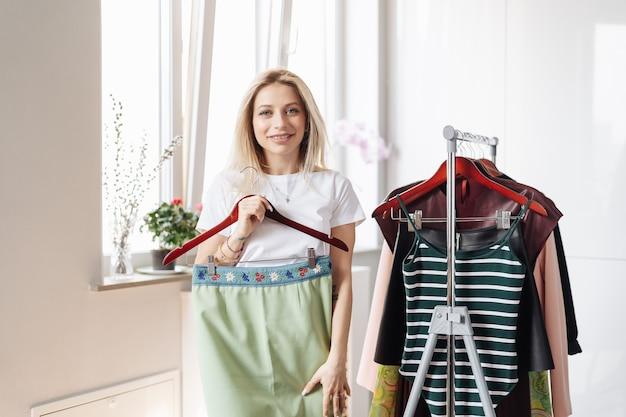 Donna che sceglie i vestiti a casa o nello showroom