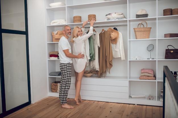 Женщина выбирает одежду в шкафу и обнимает ее муж