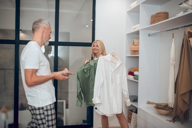 Женщина выбирает одежду в шкафу и показывает мужу