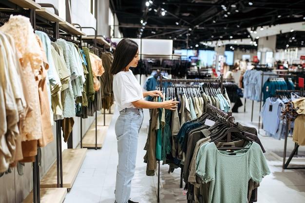 衣料品店で洋服を選ぶ女性