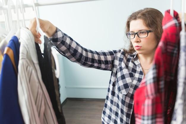 Женщина выбирает одежду перед полным шкафом