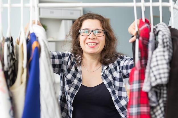 Женщина, выбирающая одежду перед полным шкафом