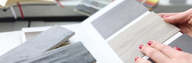 デザインスタジオのクローズアップでラミネートボードの色を選択する女性