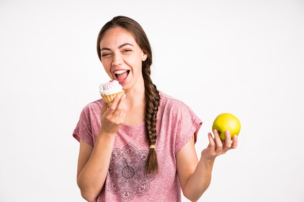 Woman choosing cupcake over apple