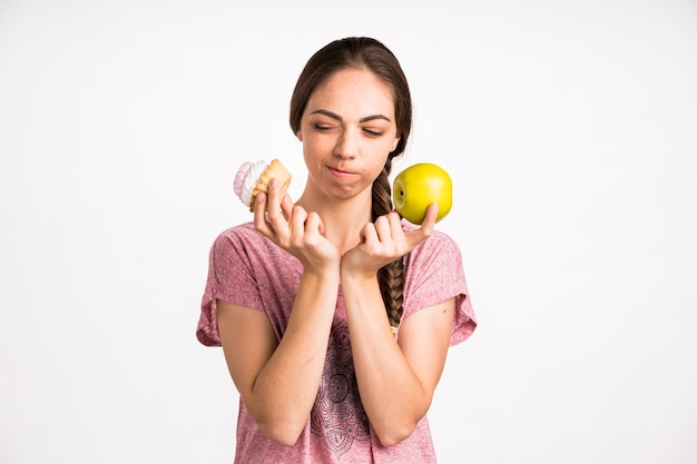 Woman choosing between cupcake and apple