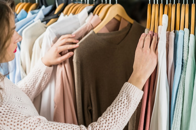 Женщина выбирая платье во время покупок в одежде одежды