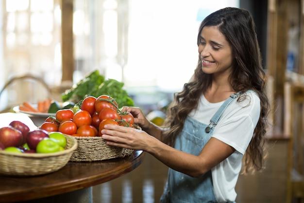 Женщина выбирает свежие помидоры из корзины