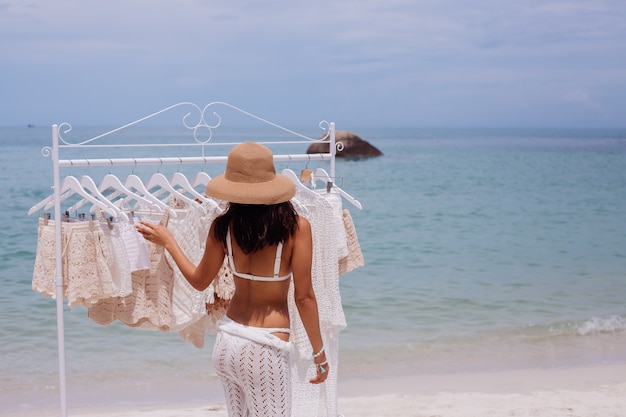 Woman choosing knitted clothes from hangers on the beach